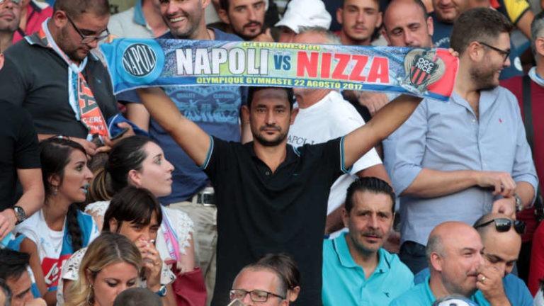 """Il Napoli batte 2-0 il Nizza nell'andata del preliminare di Champions League. Il pubblico festeggia cantando il coro """"chi non salta è juventino"""". Apparso uno striscione polemico verso la UEFA"""
